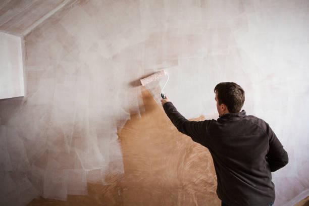 Homme qui peint un mur avec un rouleau et de la peinture blanche